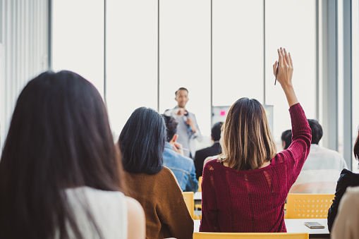 Back view business woman raising hand for asking speaker for question and answer concept in meeting room for seminar