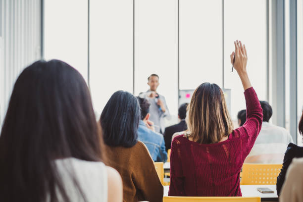 back view business woman raising hand for asking speaker for question and answer concept in meeting room for seminar - college foto e immagini stock