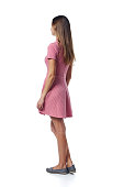 istock Back view Full length of young woman in pink dress standing casually 1146731180