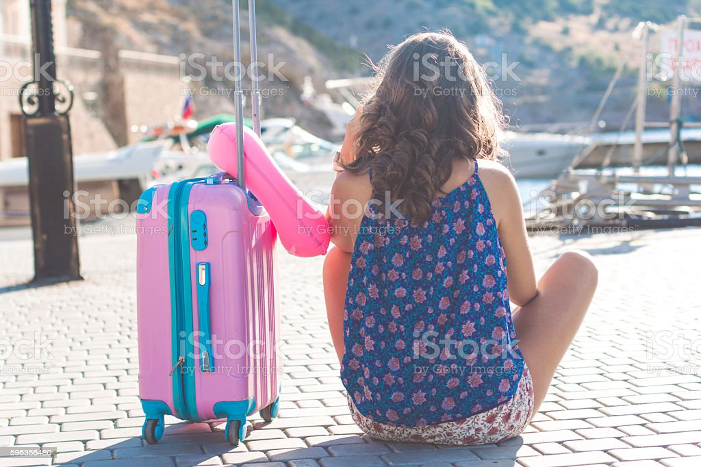 Back view girl is sitting with pink suitcase royalty-free stock photo