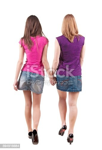 istock Back view going of two young girl (brunette and blonde) 594916684