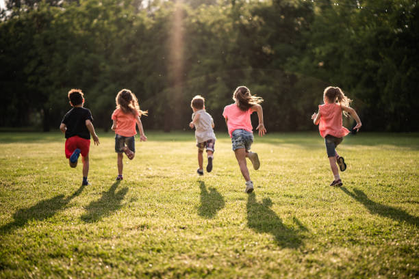 Back view group of children running in nature stock photo