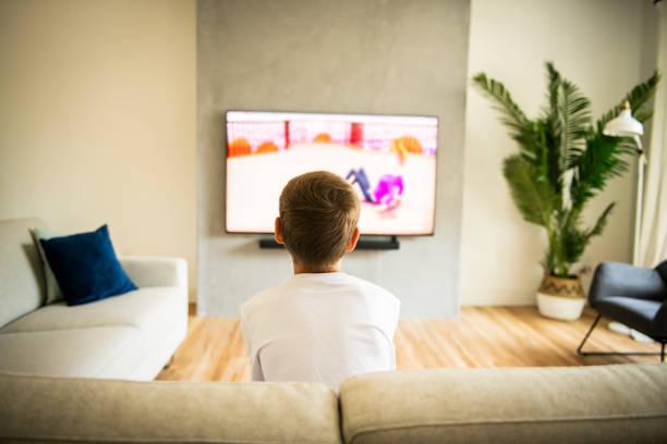 Rückansicht Bild von niedlichen Jungen sitzen auf dem Sofa und fernsehen. – Foto