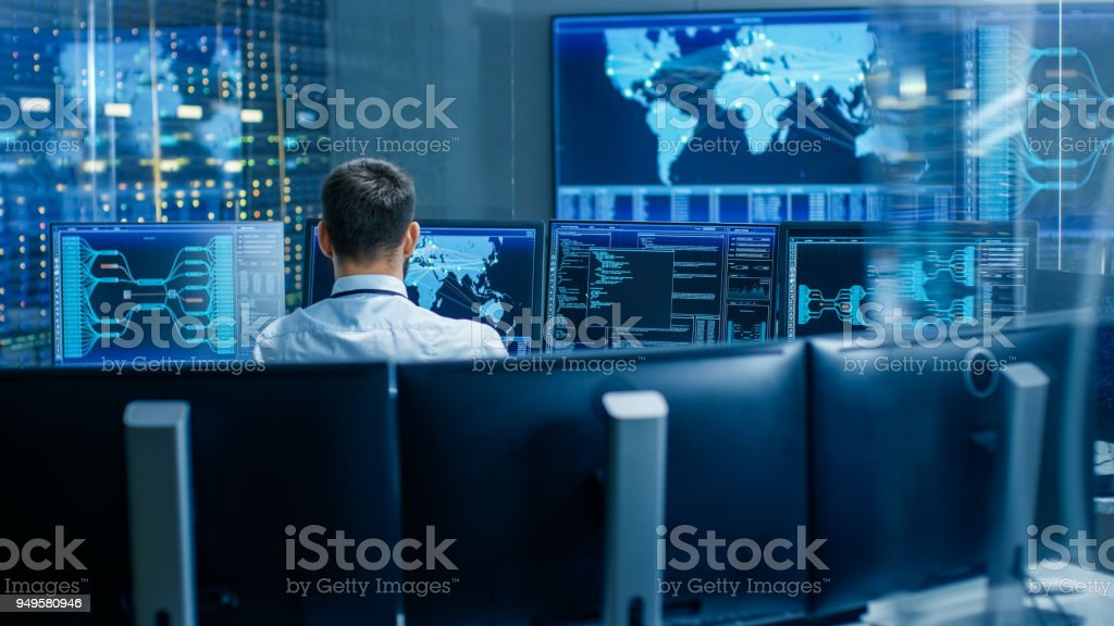 Back View in the System Control Center Operator Working. Multiple Screens Showing Technical Data. stock photo