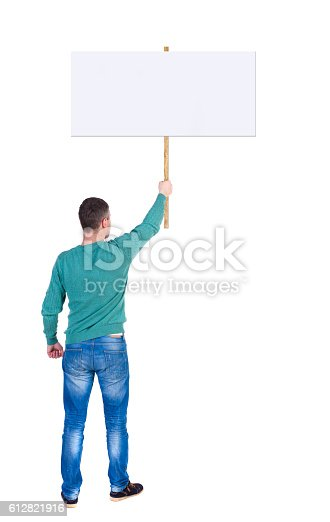 istock Back view man showing sign board. 612821916
