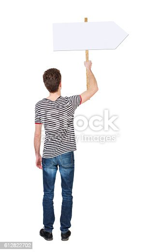 istock Back view man showing sign board. 612822702