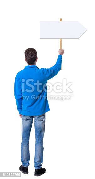 istock Back view man showing sign board. 612822766