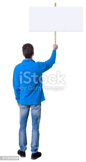 istock Back view man showing sign board. 612843008