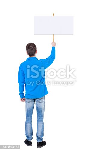 istock Back view man showing sign board. 612843164