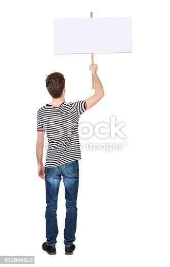 istock Back view man showing sign board. 612846522