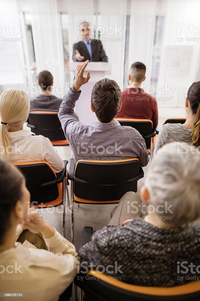 Back view of a businessman asking a question on seminar. stock photo