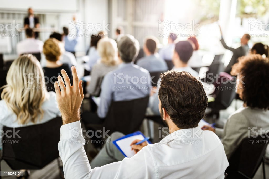 Back view of a businessman raising his hand on a seminar. - Стоковые фото Business Conference роялти-фри