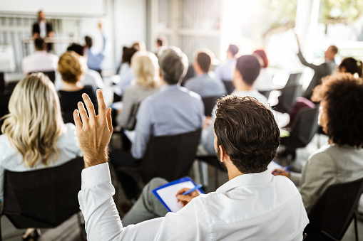 istock Back view of a businessman raising his hand on a seminar. 1148378134