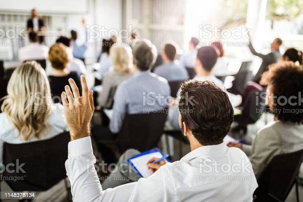 Back View Of A Businessman Raising His Hand On A Seminar — стоковые фотографии и другие картинки Business Conference