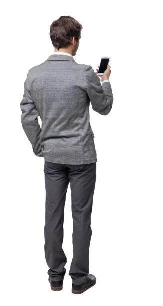 スマホを見ているビジネスマンのバックビュー。 - 背中 ストックフォトと画像
