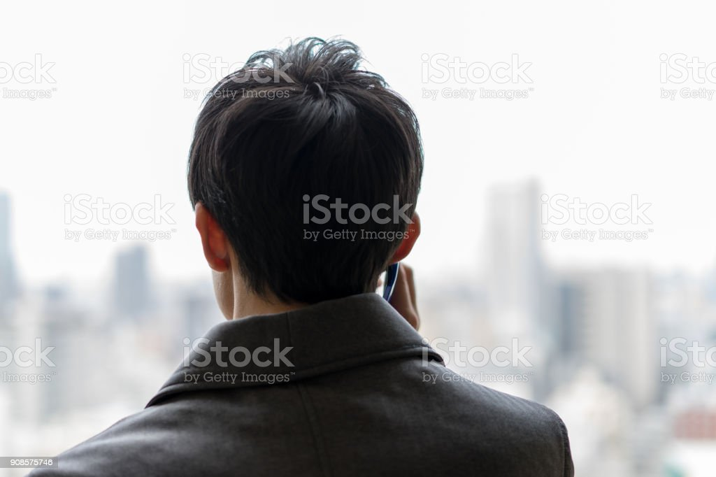 A back view of a businessman who receives a telephone call stock photo