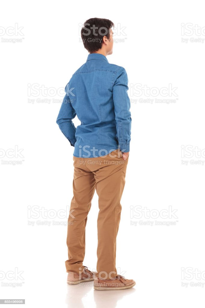 back view of a  casual man with hands in pockets stock photo