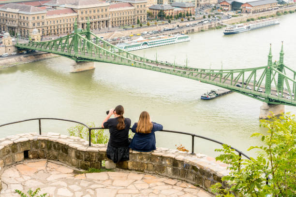 Back view of a caucasian couple sitting at a viewpoint up high taking pictures of Liberty bridge over the Danube river, Budapest. Budapest, Hungary - September 26, 2017:  Back view of a caucasian couple sitting at a viewpoint up high leaning on a steel railing taking pictures of Liberty bridge over the Danube river, Budapest Hungary. View from Gellert hill public park with the city in the background. liberty bridge budapest stock pictures, royalty-free photos & images