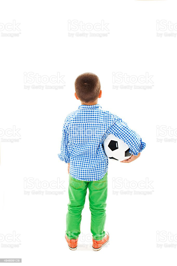Back view of a child holding a soccer ball stock photo