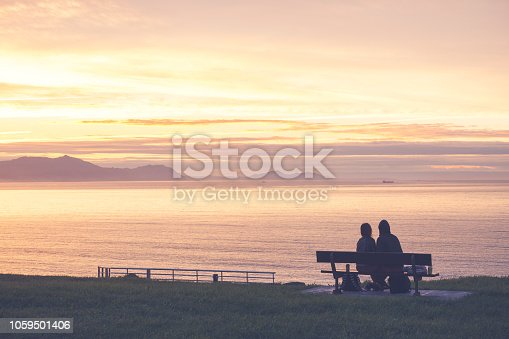 istock Back view of a couple silhouette hugging and watching sunset on the beach 1059501406