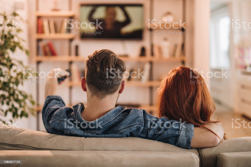 Rear view of loving couple relaxing on sofa and watching a TV at home.