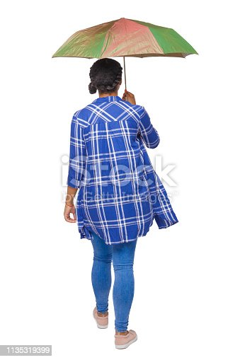 istock back view of a dark-skinned girl in a shirt walking under an umbrella. 1135319399