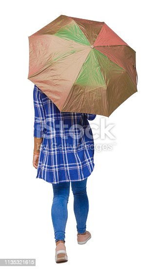 istock back view of a dark-skinned girl in a shirt walking under an umbrella. 1135321615