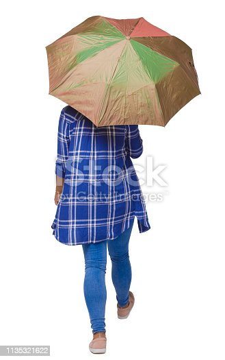 istock back view of a dark-skinned girl in a shirt walking under an umbrella. 1135321622