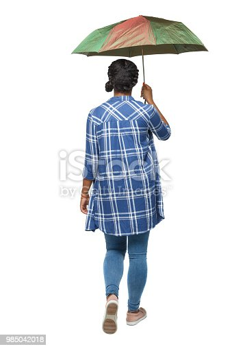istock back view of a dark-skinned girl in a shirt walking under an umbrella. 985042018
