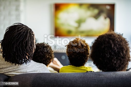 Rear view of black family relaxing on sofa while watching a movie on TV at home.