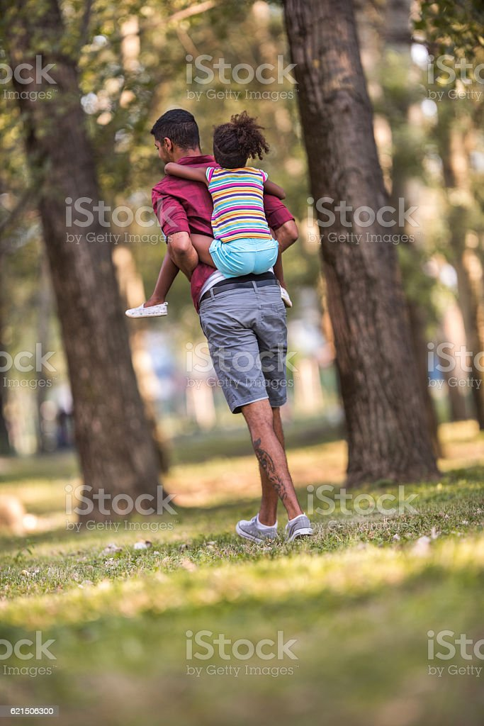 Back view of a father piggybacking his daughter in nature. photo libre de droits