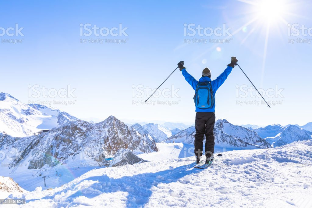 Back view of a happy skier with raised hands stock photo