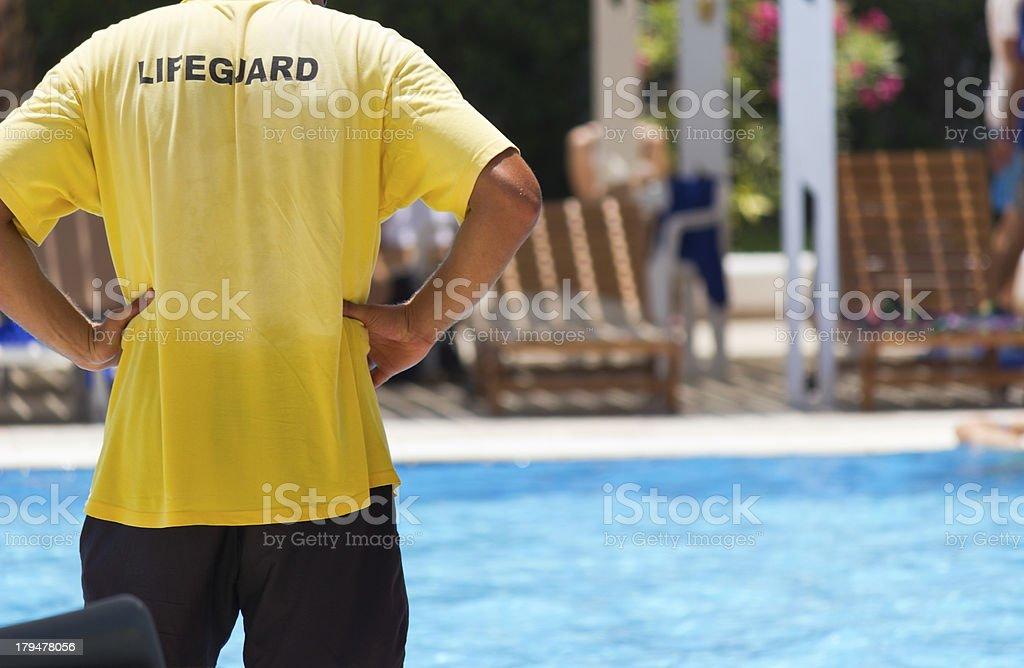Back view of a lifeguard with arms on waist watching pool stock photo