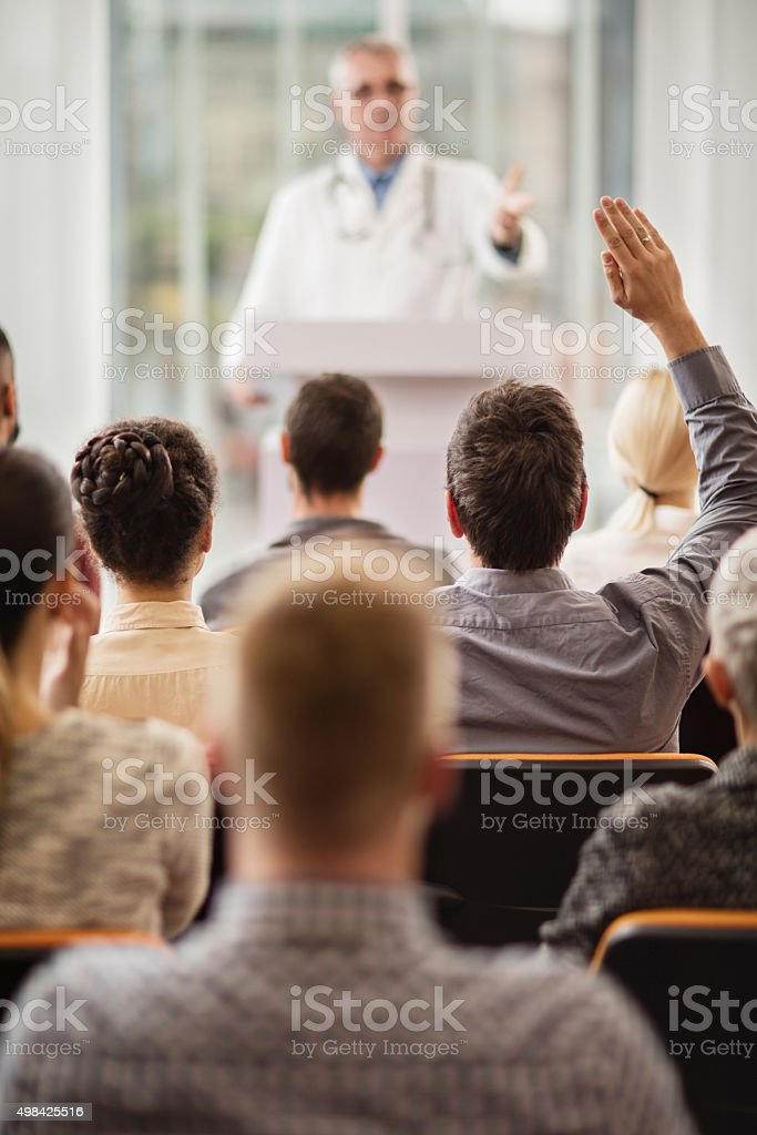 Back view of a man asking a question on seminar. stock photo