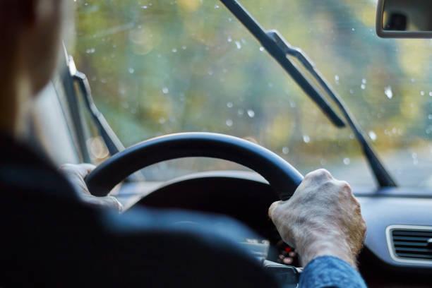 achteraanzicht van een man autorijden met bewegende ruitenwissers tijdens regen. - tractieapparaat stockfoto's en -beelden