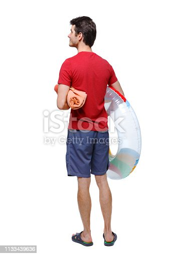 istock Back view of a man in shorts with an inflatable circle. 1133439636