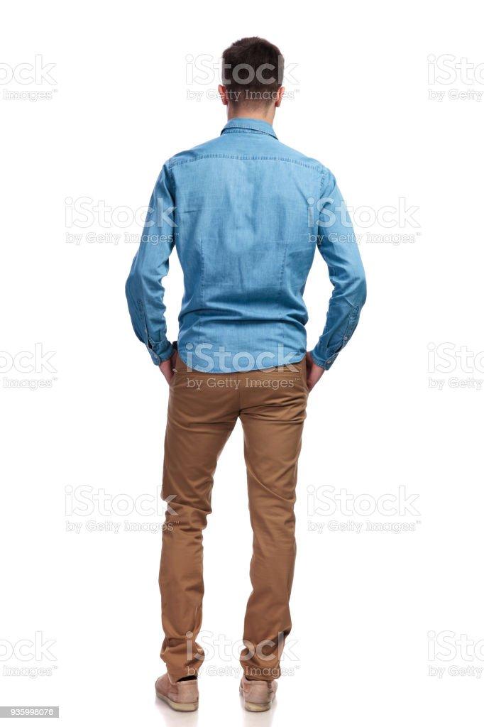 Vista posterior de un hombre de pie con las manos en los bolsillos foto de stock libre de derechos