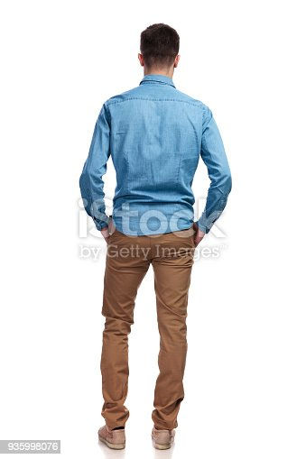 istock back view of a man standing with hands in pockets 935998076