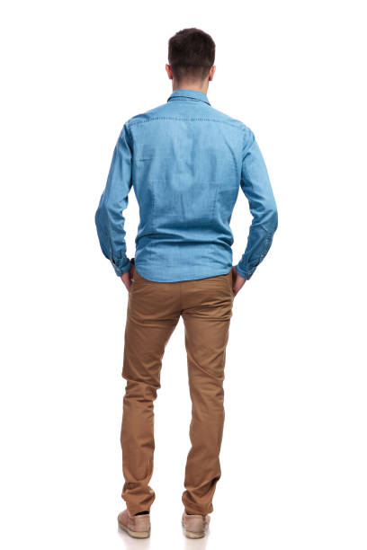 back view of a man standing with hands in pockets stock photo