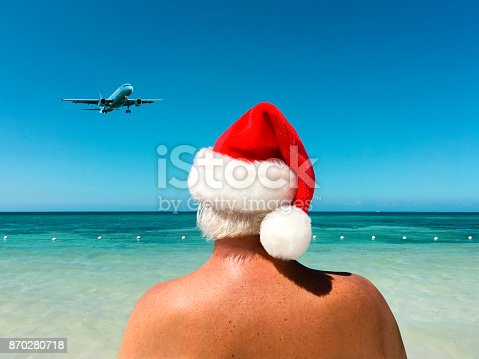 Back view of a man wearing Santa hat on a beach looking ta an airplane with a Caribbean sea background