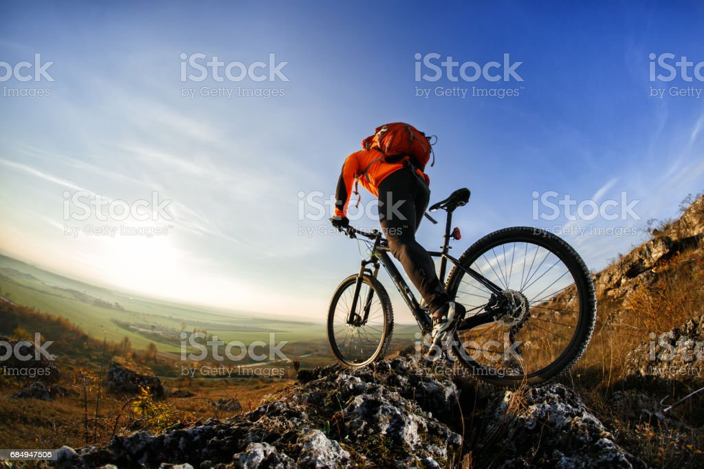 back view of a man with bicycle against the sky stock photo