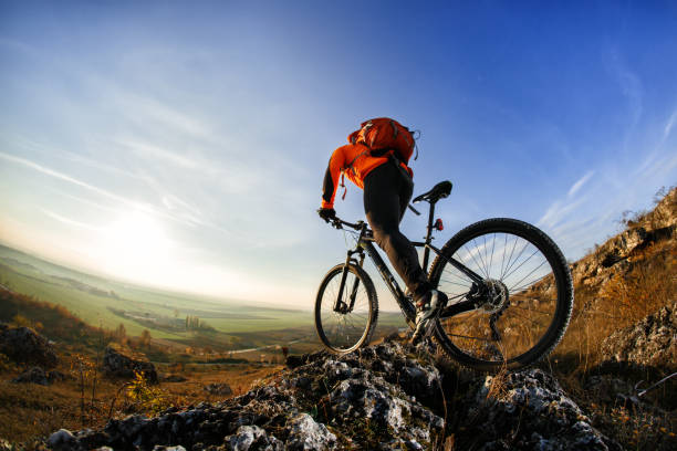 back view of a man with bicycle against the sky - mountain bike stock pictures, royalty-free photos & images