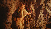 Back View of a Primitive Prehistoric Neanderthal Child in Animal Skin Draws Animals and Abstracts on the Walls at Night. Creating First Cave Art with Petroglyphs, Rock Paintings Illuminated by Fire.
