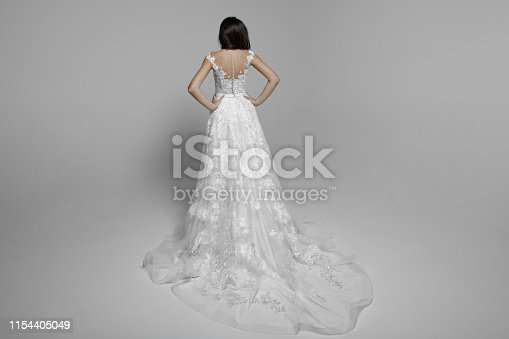 Rear view of a young woman with long hair in white beautiful wedding dress, hands on his waist, isolated on a white background.