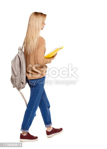istock Back view of a student walking with a backpack and textbooks. 1128060814