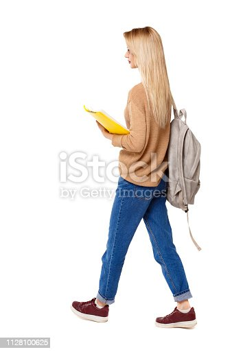 istock Back view of a student walking with a backpack and textbooks. 1128100625
