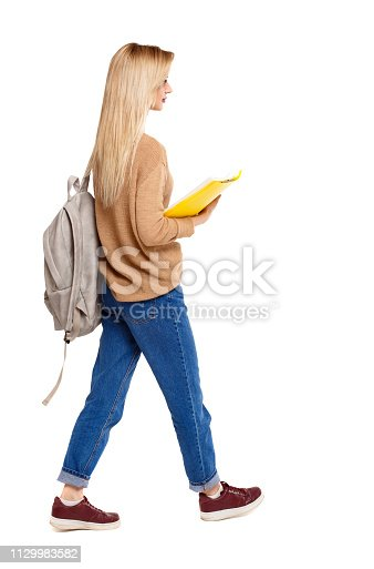 istock Back view of a student walking with a backpack and textbooks. 1129983582