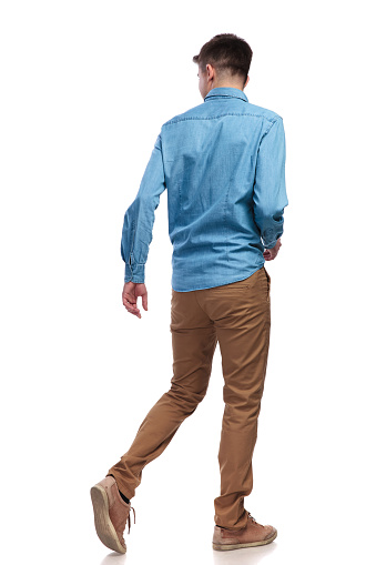 back view of a walking casual man looking to side on white background