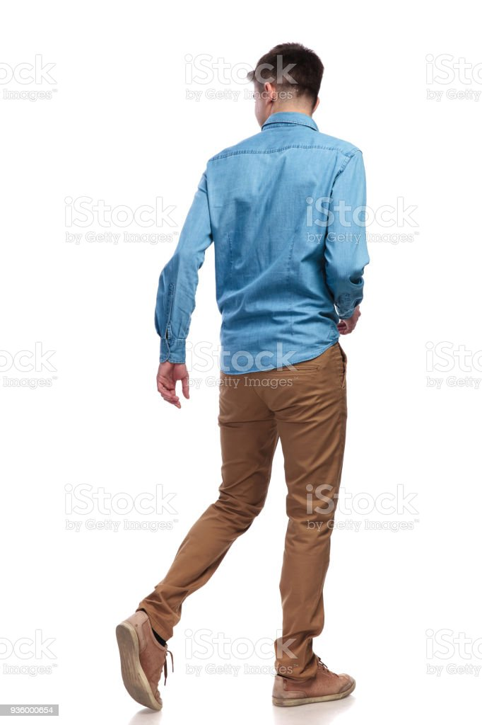 back view of a walking casual man looking to side stock photo