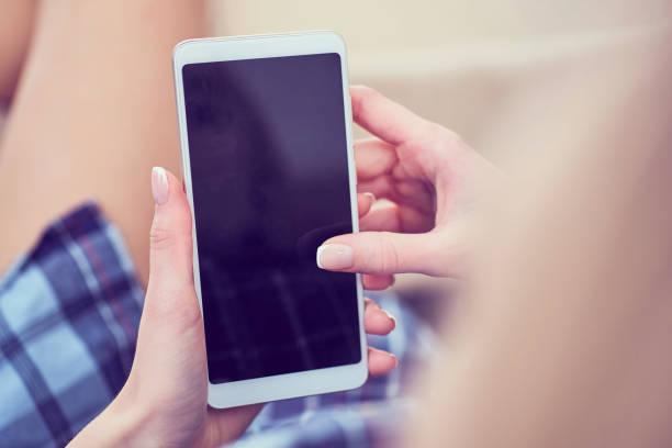 Rückansicht einer Frau Hände mit Smartphone mit leeren Bildschirm hautnah. Weiße Telefon mit einem schwarzen Bildschirm in den Händen eines jungen Mädchens, das auf dem Boden mit den Füßen auf der Couch liegen – Foto